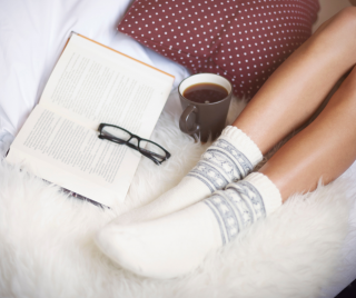 person laying on the bed with white socks on and an open book