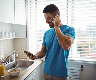 man on the kitchen calling someone on the phone