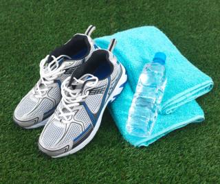 shoes and a water bottle on a folded towel