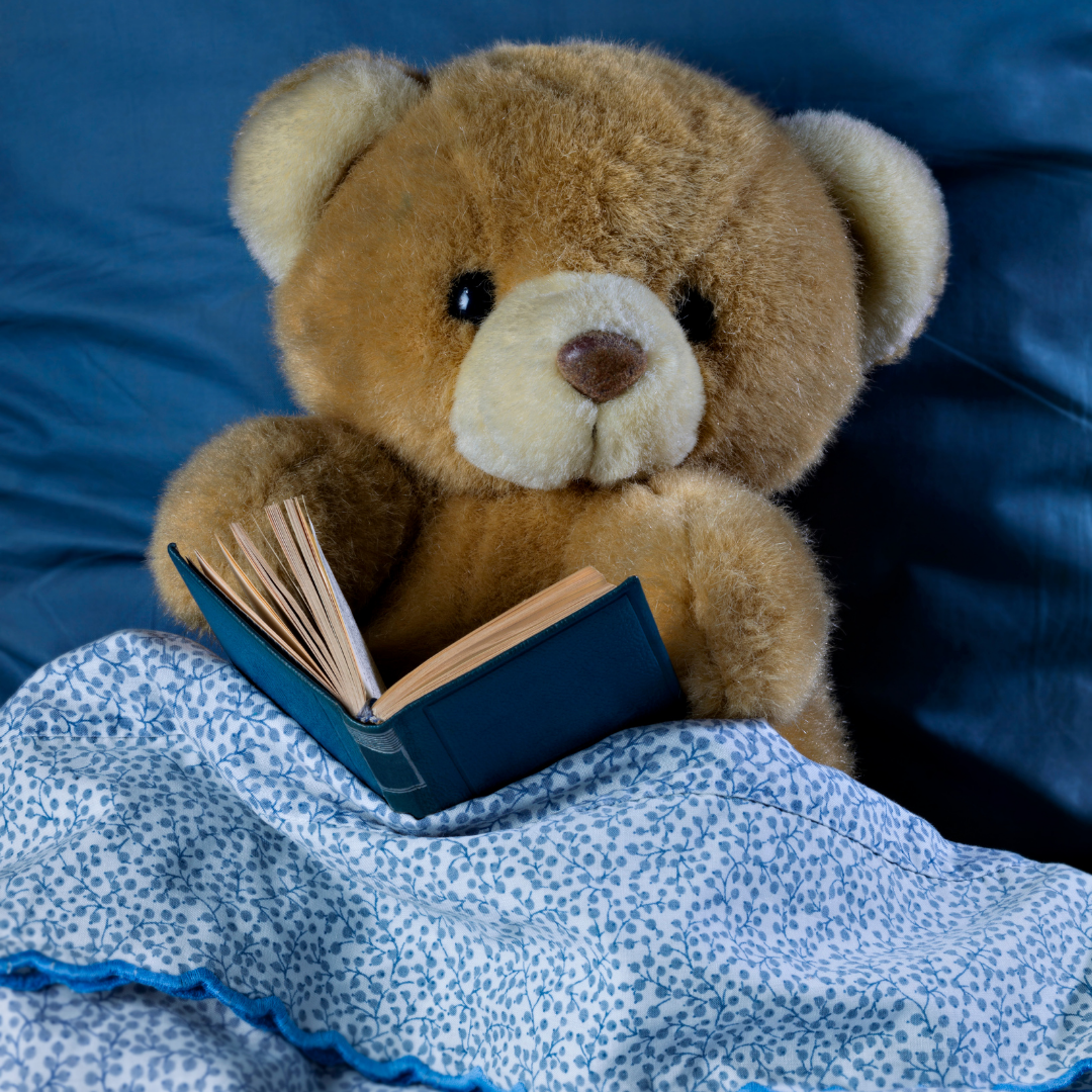 parenting kids with adhd teddy bear with a book on a bed
