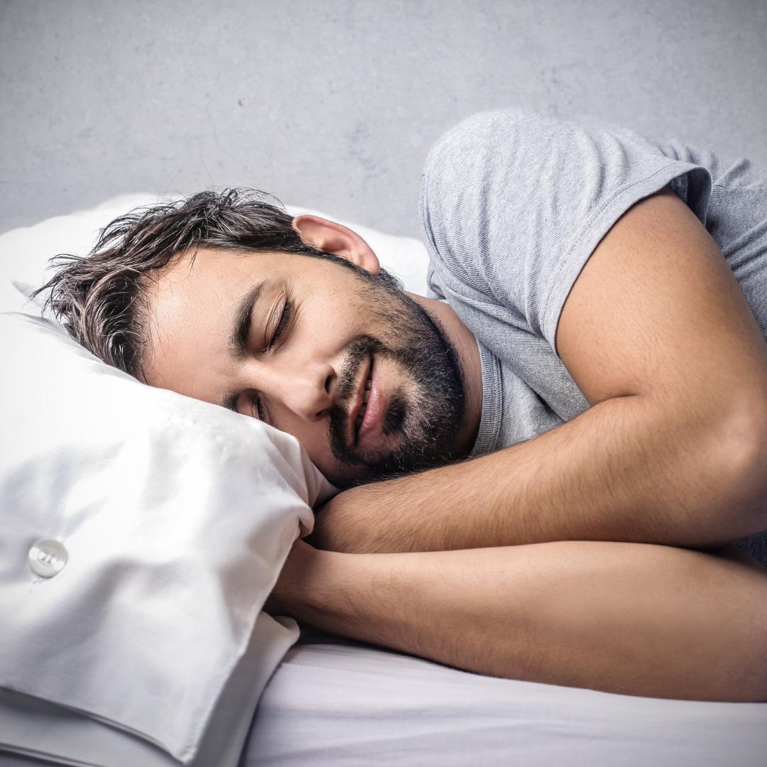 man happily sleeping on his bed lying sideways